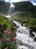 Ren liten vikvattenfall i bergen Arkivfoto