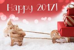 Ren mit Schlitten, roter Hintergrund, simsen glückliches 2017 Stockfotos