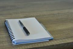 Ren notepad med en penna på ett träskrivbord arkivbilder