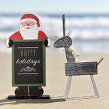 Ren och Santa Claus med lyckliga ferier för text på stranden Royaltyfri Bild