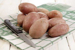 Ren potatis och kökkniv på en kökshandduk Royaltyfri Bild