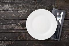 ren tom vit platta, gaffel och kniv på den gråa gamla lantliga trätabellen, kopieringsutrymme, åtlöje upp, bästa sikt arkivfoto