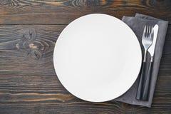 ren tom vit platta, gaffel och kniv på den mörka lantliga trätabellen, kopieringsutrymme, åtlöje upp, bästa sikt royaltyfri fotografi