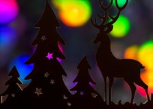 Ren- und Weihnachtsbaumausschnittschattenbild mit mehrfarbigem bokeh Hintergrund lizenzfreie stockbilder