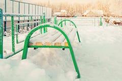 Ren vit snö ackumulerar på en grön bänk i en solig dag för vinter arkivfoton