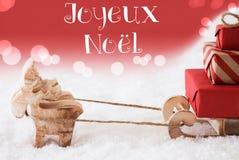 Rena com trenó, fundo vermelho, Joyeux Noel Means Merry Christmas Fotografia de Stock Royalty Free