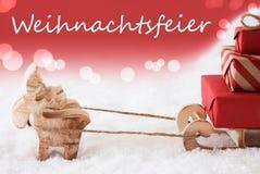 A rena com trenó, fundo vermelho, Weihnachtsfeier significa a festa de Natal Foto de Stock