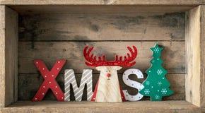Rena de madeira da decoração dos símbolos do Natal com texto do xmas foto de stock