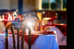 Rena glass bägare och exponeringsglas är på tabellen med en vit bordduk och röda servetter arkivbild
