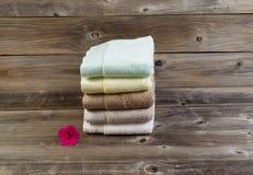 Rena handdukar och enkla rosa färger blommar på Weathered trä Arkivfoto