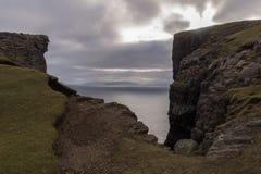 Rena klippor med dramatisk himmel på den Vagar ön, Faroe Island, Danmark arkivbilder