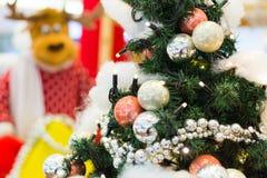 Rena que está por uma árvore de Natal Imagens de Stock