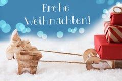 Rena, trenó, luz - o fundo azul, Frohe Weihnachten significa o Feliz Natal Fotografia de Stock Royalty Free