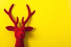 Rena vermelha decorativa de veludo em um fundo amarelo Foto de Stock Royalty Free