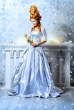 Renaissance beauty. Elegant young woman in a lush white medieval dress with red hair in the style of the Renaissance. Beautiful Ice Queen in her snow palace Royalty Free Stock Images