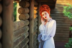 Renaissance princess in white gown. Beautiful redhead victorian girl with red hair in old white dress in palace. Victorian era his. Toric costume. White stock photos