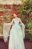 Renaissance redhead princess with hairstyle in corset. Renaissance queen with magic hairdo against stone wall. Victorian doll. Fantasy princess in historic stock photo