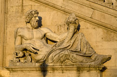 Renaissance sculpture of the man holding the Cornucopia. Sculpture lit by the soft evening sun in Rome Stock Image