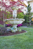 Renaissance Water Fountain in Front Lawn. Renaissance Water Fountain on Front Lawn Landscaping with Trees and Flowering Shrubs Royalty Free Stock Photo