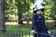 Renaissancevrouw met boek op de brug in het park Royalty-vrije Stock Foto's