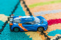 Renault Alpina toy car. Blue Renault Alpina racing toy car of the Burago brand on a carpet in soft focus Royalty Free Stock Photos