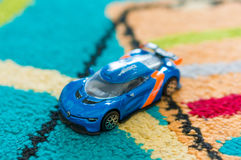 Renault Alpina toy car. Blue Renault Alpina racing toy car of the Burago brand on a carpet in soft focus Stock Images