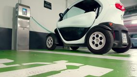 Renault Twizy Electric Car responsable dans un stationnement souterrain banque de vidéos