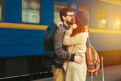 Rencontre après un voyage d'un couple heureux étreignant dans la rue dans une station de train Lumière du soleil chaude de belle  Image stock