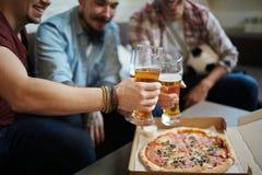 Rencontrer d'amis la bière et la pizza Photographie stock libre de droits