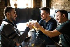 Rencontrer les meilleurs amis Trois jeunes hommes heureux dans la tenue de détente parlant et bière potable tout en se reposant d Photos libres de droits