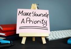 Renda una priorità scritta a mano su pezzo di carta fotografia stock