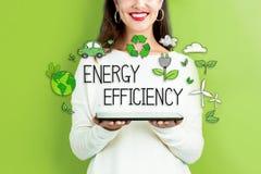 Rendement énergétique avec la femme tenant un comprimé photographie stock libre de droits