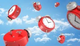 rendição 3d de muitos despertadores retros redondos vermelhos que caem para baixo no fundo de um céu azul com nuvens brancas Foto de Stock Royalty Free