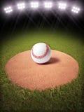 rendição 3d de um basebol em um monte de jarros do campo de basebol Lighted Imagem de Stock