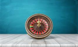 a rendição 3d de uma roleta do casino está em seu lado em uma mesa de madeira na frente de um fundo azul Imagem de Stock