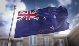 Rendição da bandeira 3D da bandeira de Nova Zelândia no céu azul que constrói Backgrou Fotografia de Stock Royalty Free