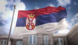 Rendição da bandeira 3D da Sérvia no fundo da construção do céu azul Fotos de Stock