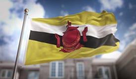 Rendição da bandeira 3D de Brunei Darussalam no fundo da construção do céu azul Fotografia de Stock Royalty Free