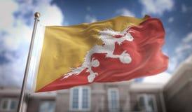 Rendição da bandeira 3D de Butão no fundo da construção do céu azul Imagens de Stock