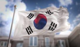 Rendição da bandeira 3D de Coreia do Sul no fundo da construção do céu azul Imagem de Stock Royalty Free
