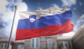 Rendição da bandeira 3D de Eslovênia no fundo da construção do céu azul Foto de Stock