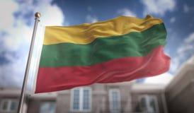 Rendição da bandeira 3D de Lituânia no fundo da construção do céu azul Fotos de Stock Royalty Free