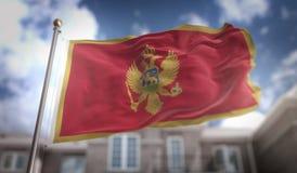 Rendição da bandeira 3D de Montenegro no fundo da construção do céu azul Imagem de Stock Royalty Free