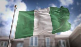 Rendição da bandeira 3D de Nigéria no fundo da construção do céu azul Foto de Stock Royalty Free