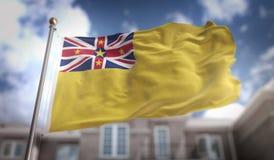 Rendição da bandeira 3D de Niue no fundo da construção do céu azul Foto de Stock