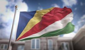 Rendição da bandeira 3D de Seychelles no fundo da construção do céu azul Imagens de Stock Royalty Free