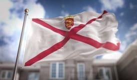 Rendição da bandeira 3D do jérsei no fundo da construção do céu azul Imagem de Stock Royalty Free