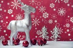 Rendier op rode achtergrond en ornamenten Stock Foto's
