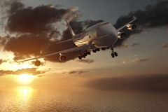 rendu 3d d'une vue de face d'une grande avion de ligne dans un coucher du soleil au-dessus de l'océan Photos stock