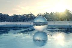 rendu 3d de boule de cristal sur le lac congelé dans le sunli de soirée Photos libres de droits